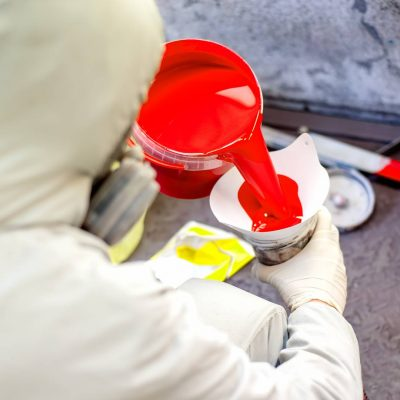 auto-mechanic-mixing-and-pouring-red-paint-for-PPDNZ5F-1